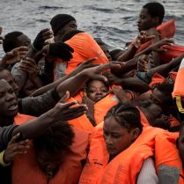 Rubber boat full of migrants as life jackets are being distributed by the MOAS crew. As they often don't have life jackets and do not know how to swim, the first priority if making sure everybody is given a floatation device. 2016 was a deadly year of migrants and refugees trying to cross the mediterranean from Libya's coasts to Italy's. With ever increasing numbers of unseaworthy boats attempting the crossing, charities and NGOs like MOAS are often overwhelmed. MOAS, together with medicals teams from the red cross, operates two rescue vessels, the Responder and the Phoenix, just off the coast of Libya. They sit in international waters and await either the distress call from migrants lucky enough to have been given a satellite phone by their smuggler, or to visually find migrants boats - often in the dead of night. Then the race to rescue them before it too late starts.