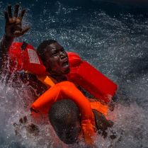 Two men panic and struggle in the water during their rescue. Their rubber boat was in distress and deflating quickly on one side, tipping many migrants in the water. They were quickly reached by rescue swimmers and brought to safety. 2016 was a deadly year of migrants and refugees trying to cross the mediterranean from Libya's coasts to Italy's. With ever increasing numbers of unseaworthy boats attempting the crossing, charities and NGOs like MOAS are often overwhelmed. MOAS, together with medicals teams from the red cross, operates two rescue vessels, the Responder and the Phoenix, just off the coast of Libya. They sit in international waters and await either the distress call from migrants lucky enough to have been given a satellite phone by their smuggler, or to visually find migrants boats - often in the dead of night. Then the race to rescue them before it too late starts. © Mathieu Willcocks/MOAS.eu 2016, all rights reserved.